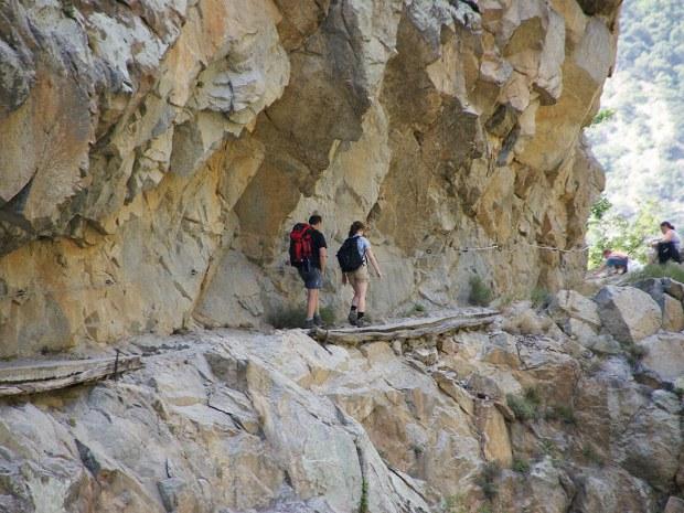 Zwei Wanderer gehen an einer Bergwand entlang