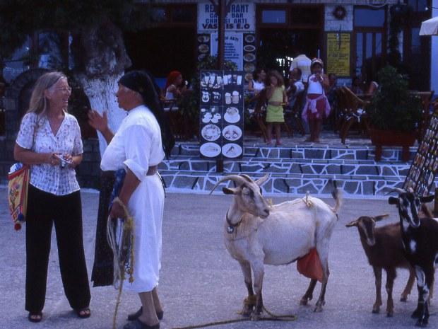 Zwei Frauen unterhalten sich auf einem Marktplatz neben einem Ziegenbock