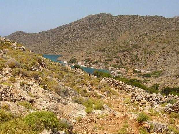 Landschaft mit Büschen und Steinen und einem See